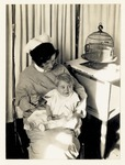 Student nurse feeding a baby